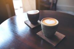 Deux petites tasses de café chaud de latte avec l'art de latte sur la table en bois de cru en café photos libres de droits