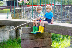 Deux petits amis adorables pêchant avec la tige selfmade Image libre de droits