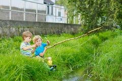 Deux petits amis adorables pêchant avec la tige selfmade Photos libres de droits