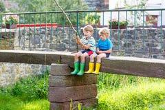 Deux petits amis adorables pêchant avec la tige selfmade Photos stock