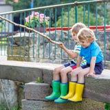 Deux petits amis adorables pêchant avec la tige selfmade Photo stock