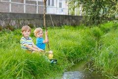 Deux petits amis adorables pêchant avec la tige selfmade Photographie stock
