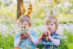 Deux petits amis avec les oreilles de lapin de Pâques et le chocolat de consommation Images stock