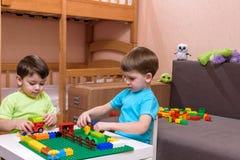 Deux petits amis caucasiens jouant avec un bon nombre de blocs en plastique colorés d'intérieur Garçons actifs d'enfant, enfants  Image stock