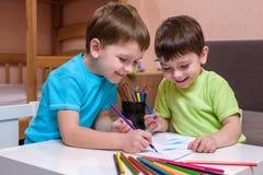 Deux petits amis caucasiens jouant avec un bon nombre de blocs en plastique colorés d'intérieur Garçons actifs d'enfant, enfants  Photographie stock libre de droits
