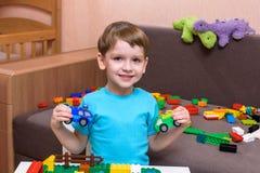 Deux petits amis caucasiens jouant avec un bon nombre de blocs en plastique colorés d'intérieur Garçons actifs d'enfant, enfants  Photos stock