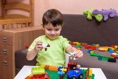 Deux petits amis caucasiens jouant avec un bon nombre de blocs en plastique colorés d'intérieur Garçons actifs d'enfant, enfants  Photo stock