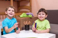 Deux petits amis caucasiens jouant avec un bon nombre de blocs en plastique colorés d'intérieur Garçons actifs d'enfant, enfants  Photo libre de droits