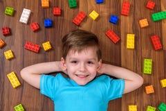 Deux petits amis caucasiens jouant avec un bon nombre de blocs en plastique colorés d'intérieur Garçons actifs d'enfant, enfants  Image libre de droits