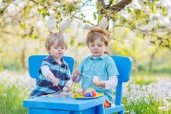 Deux petits amis dans des oreilles de lapin de Pâques colorant des oeufs Image stock