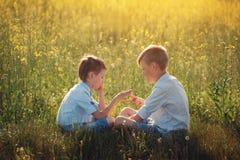 Deux petits amis jouant - pierre, ciseaux, jeu de papier dans le jour d'été Images stock
