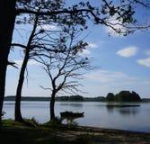 Deux petits bateaux et arbres foncés par le lac au secteur polonais de Masuria (Mazury) Photo stock