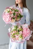 Deux petits beaux bouquets des fleurs m?lang?es chez la main de la femme Concept floral de boutique Beau bouquet coup? frais Fleu photographie stock libre de droits