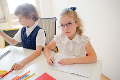 Deux petits disciples d'une école primaire s'asseyent au bureau Photos libres de droits
