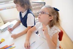 Deux petits disciples d'une école primaire s'asseyent au bureau Images libres de droits