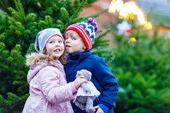 Deux petits enfants étreignant sur le marché de Noël Image stock