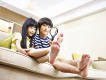 Deux petits enfants asiatiques jouant avec une loupe à la maison Photos stock