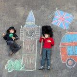 Deux petits enfants avec Londres décrivent le dessin avec des craies Images libres de droits