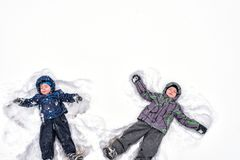Deux petits enfants de mêmes parents badinent des garçons dans des vêtements colorés d'hiver faisant s Photo stock