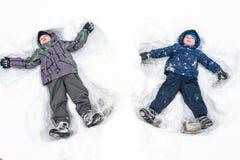 Deux petits enfants de mêmes parents badinent des garçons dans des vêtements colorés d'hiver faisant s Photographie stock