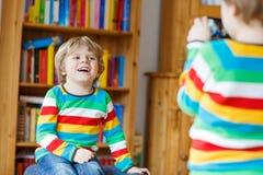 Deux petits enfants de mêmes parents badinent des garçons faisant des photos avec le photocamera, dedans Images stock