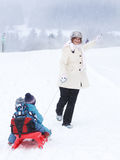 Deux petits enfants de mêmes parents et leur mère ayant l'amusement sur le traîneau sur la victoire Image stock
