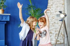 Deux petits enfants drôles dansent et chantent une chanson dans le karaoke E images stock