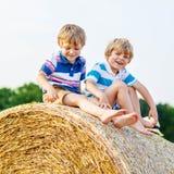 Deux petits enfants et amis avec la pile ou la balle de foin Photographie stock