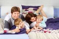 Deux petits enfants et parents ayant l'amusement dans le lit images stock