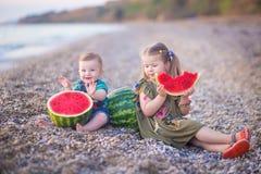 Deux petits enfants, fille de garçon, mangeant la pastèque sur la plage, été appréciant le beau jour près de l'océan photos libres de droits