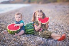 Deux petits enfants, fille de garçon, mangeant la pastèque sur la plage, été appréciant le beau jour près de l'océan photo stock