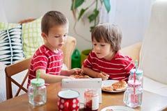 Deux petits enfants, frères de garçon, mangeant le petit déjeuner à la maison, whil image stock