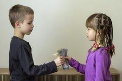 Deux petits enfants garçon et fille jouant avec l'argent des dollars Photographie stock