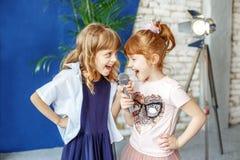 Deux petits enfants heureux chantent une chanson dans le karaoke Le concept est photo stock