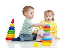 Deux petits enfants jouant avec des jouets de couleur Image stock