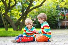 Deux petits enfants jouant avec l'autobus scolaire rouge Photographie stock libre de droits
