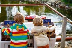 Deux petits enfants jouant avec les bateaux commandés par radio Image libre de droits