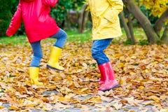 Deux petits enfants jouant dans des bottes en caoutchouc rouges et jaunes en automne se garent Image libre de droits