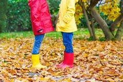 Deux petits enfants jouant dans des bottes en caoutchouc rouges et jaunes en automne se garent Photographie stock