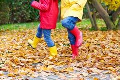 Deux petits enfants jouant dans des bottes en caoutchouc rouges et jaunes en automne se garent Image stock