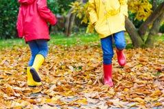 Deux petits enfants jouant dans des bottes en caoutchouc rouges et jaunes en automne se garent Photos libres de droits