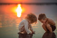 Deux petits enfants jouant sur la plage pendant le coucher du soleil Réflexion dans l'eau Photo libre de droits