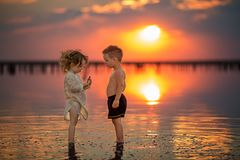 Deux petits enfants jouant sur la plage pendant le coucher du soleil Réflexion dans l'eau Image libre de droits