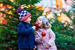 Deux petits enfants mangeant la pomme crystalized sur le marché de Noël Image stock