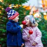 Deux petits enfants mangeant la pomme crystalized sur le marché de Noël Image libre de droits