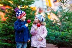 Deux petits enfants mangeant la pomme crystalized sur le marché de Noël Images libres de droits