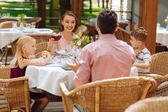Deux petits enfants prenant le petit déjeuner de famille avec des parents Photo stock