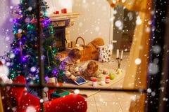 Deux petits enfants s'asseyant par une cheminée à la maison sur Noël Images stock