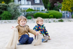 Deux petits enfants s'asseyant sur la plage de la rivière Elbe et jouant t Photos stock