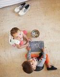 Deux petits enfants s'asseyant sur le plancher et le dessin Photographie stock libre de droits